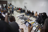FILE - In this July 8, 2021 file photo, suspects in the assassination of Haiti's President Jovenel Moise are shown to the media, along with the weapons and equipment they allegedly used in the attack, at police headquarters in Port-au-Prince, Haiti. Haitian authorities have implicated at least 20 retired Colombian soldiers in the president's assassination on July 7. (AP Photo/Jean Marc Hervé Abélard, File)