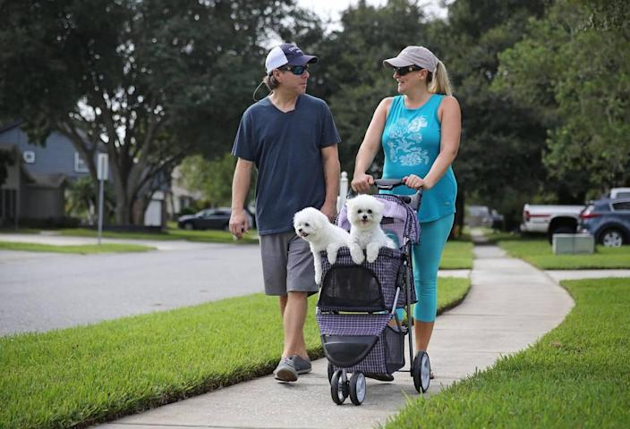 James and Lindsey Johnson walk Mako and Kona through their Winter Park neighborhood. The dogs bring the couple much joy and have helped assuage the grief over the loss of their son.