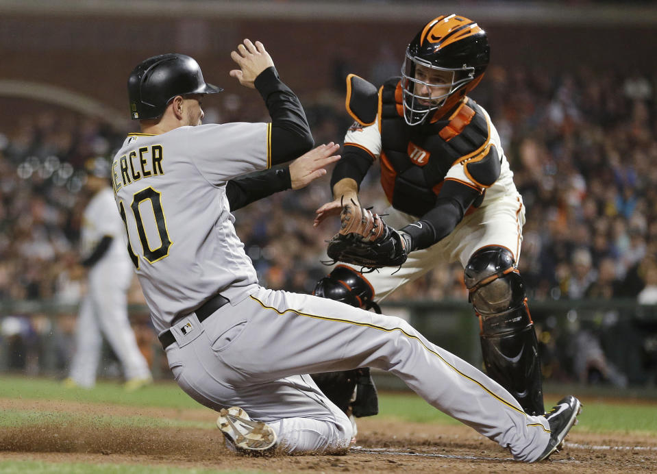 FILE - In this Aug. 9, 2018, file photo, San Francisco Giants catcher Buster Posey tags out the Pittsburgh Pirates' Jordy Mercer in a baseball game in San Francisco. San Francisco will be younger, with fewer big names, for sure. And some of those big names _ take Buster Posey, Brandon Belt and Madison Bumgarner _ are eager for fresh starts after injury-shortened years in 2018. (AP Photo/Eric Risberg, File)