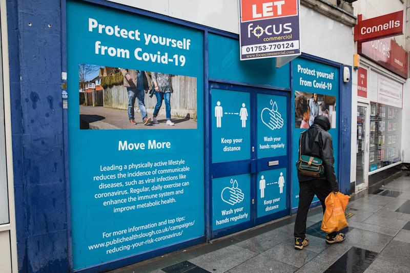 A member of the public passes COVID-19 public information displays on 4 October 2020 in Slough, United Kingdom. Slough Borough Council confirmed on 2nd October that its coronavirus infection rate is the highest in the south of England and Slough MP Tan Dhesi asked Health Secretary Matt Hancock in Parliament whether the local test centre in Montem Lane could be reverted to permit walk-in and drive-in visits without an appointment. (photo by Mark Kerrison/In Pictures via Getty Images)