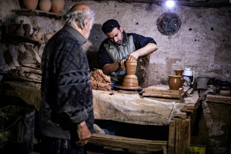 "Petros watches his son Anto moulding a clay vase and says he must keep his hands balanced like a trapeze artist ""walking on a tight rope"""