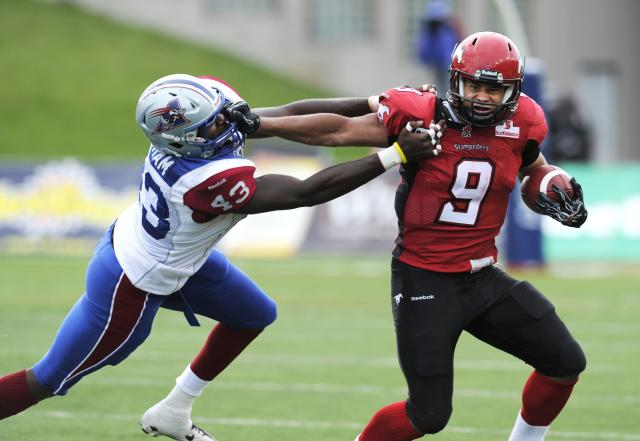 Calgary Stampeders' Jon Cornish, right, breaks from Momtreal Alouettes' Kenny Ingram during second half CFL acton in Calgary on Friday July 1st, 2011. CFL PHOTO-Larry MacDougal