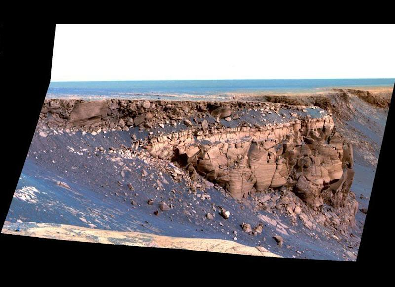 "The exploration of Victoria crater by Opportunity revealed some of the most dramatic and picturesque landscapes yet encountered by either rover. This Pancam sol 1167 (May 7, 2007) false-color mosaic shows some of the steep, layered cliffs of the promontory called Cape of Good Hope. <em>From ""Postcards from Mars"" by Jim Bell; Photo credit: NASA/JPL/Cornell University</em>"