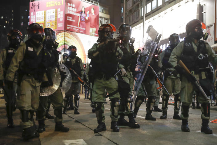 Riot police officer aims his tear gas gun at protesters on the street of Yuen Long, Hong Kong, Monday, Oct. 21, 2019. A evening sit-in at a suburban train station on the three-month anniversary of a violent attack there on protesters by men with suspected organized crime ties. (AP Photo/Mark Schiefelbein)