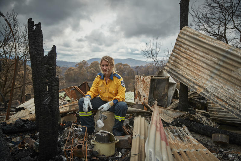 Rural Fire Service volunteer, Anika Craney, goes through the burned ruins of her home in Cobargo.