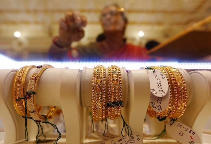FILE PHOTO: Gold bangles are on display as a woman makes choices at a jewellery showroom during Dhanteras, a Hindu festival associated with Lakshmi, the goddess of wealth, in Kolkata, India