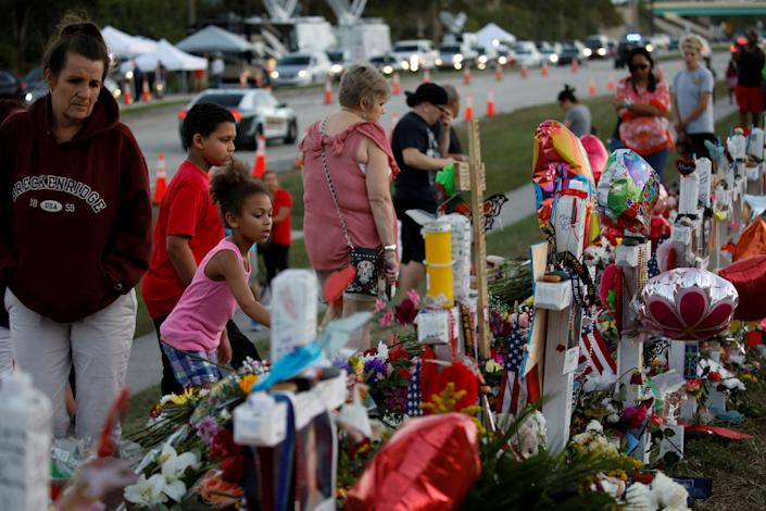 People grieve in front of crosses and Stars of David placed in front of the fence of the Marjory Stoneman Douglas High School to commemorate the victims of the mass shooting, in Parkland, Florida, U.S., Feb. 21, 2018 (Photo: Carlos Garcia Rawlins / Reuters)