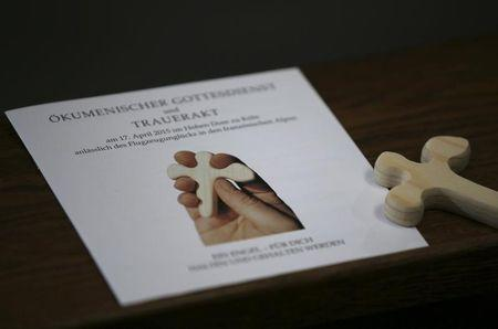 A small wooden cross in a shape of an angel and a programme are pictured at a memorial service for the 150 victims of Germanwings flight 4U 9525 in Cologne's Cathedral, April 17, 2015. REUTERS/Oliver Berg/Pool