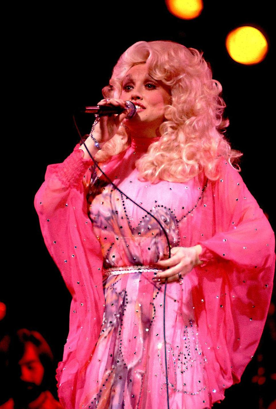 <p>Here, Parton is dressed up like the fourth fairy godmother in <em>Sleeping Beauty</em>. </p>