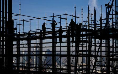 Construction workers are silhouetted while standing on scaffolding at the construction site of the new headquarters of the  ECB during a guided media tour in Frankfurt