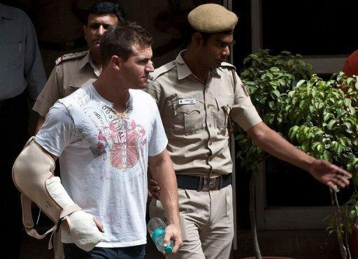 Delhi policemen escort Australian cricketer Luke Pomersbach (C) to a court appearance in New Delhi