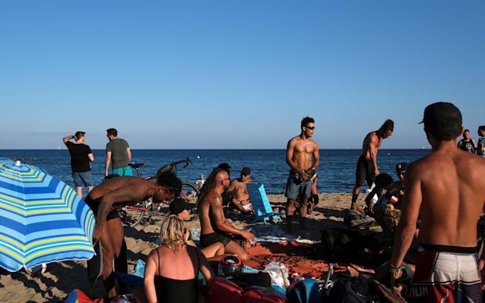 People enjoy the sunny weather at Barceloneta beach, Spain - Nacho Doce / Reuters
