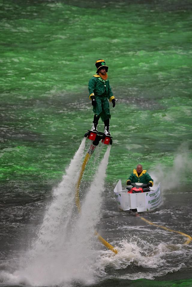 CHICAGO, IL - MARCH 16: A man dressed as a leprechaun entertains the crowd on a water propelled Flyboard while workers dye the Chicago River green to kick off the city's St. Patrick's day celebration on March 16, 2013 in Chicago, Illinois. The dying of the river has been a tradition in the city for 43 years. (Photo by Scott Olson/Getty Images)