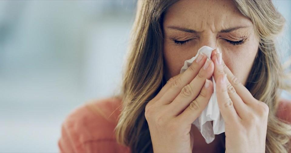 Woman feeling ill and blowing her nose with a tissue at home.