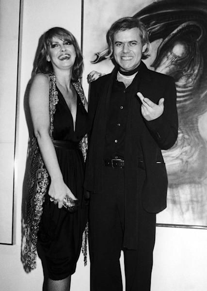 "FILE - In this April 1980 file photo, Swiss artist H.R. Giger, right, poses with model Anneka Vasta at the opening of an exhibition in New York. H.R. Giger, who designed the creature in Ridley Scott's sci-fi horror classic ""Alien,"" has died at age 74 from injuries suffered in a fall. Sandra Mivelaz, administrator of the H.R. Giger museum in Chateau St. Germain told The Associated Press Tuesday May 13, 2014 that Giger had died in a hospital the day before. Giger received a 1979 Academy Award for special effects in 'Alen'. (AP Photo/Bocklett,File)"