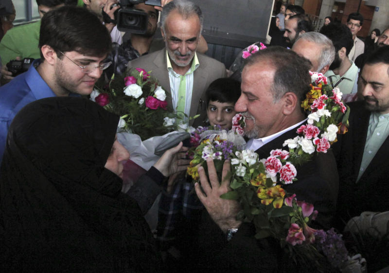 Iranian scientist, Mojtaba Atarodi, center right, who was in U.S.  custody since late 2011 over allegations he bought high-tech equipment in violation of U.S. sanctions on Iran, is welcomed by his family, upon his arrival at the Imam Khomeini airport outside Tehran, Iran, Saturday, April 27, 2013. Atarodi arrived home via Oman, a Gulf state which has served as a mediator between Washington and Tehran before. (AP Photo/Vahid Salemi)