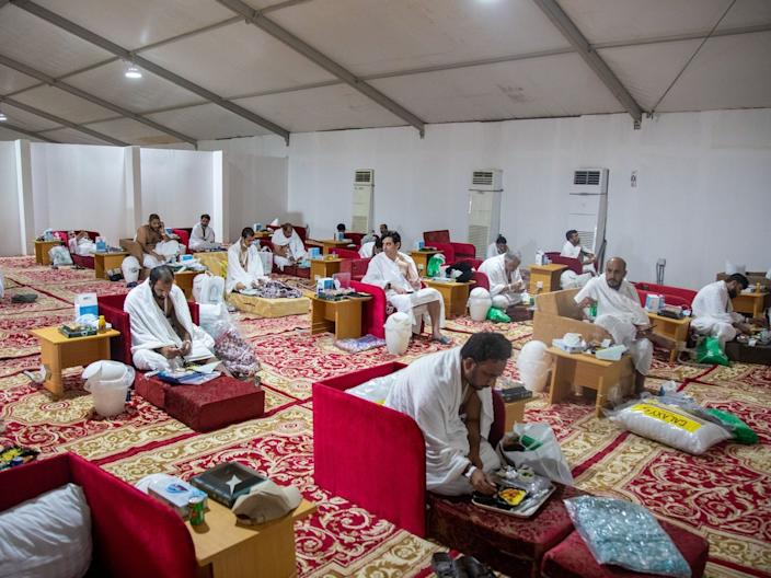 Muslim pilgrims receive food as they sit in a tent on the plains of Arafat during the annual Hajj pilgrimage, on July 30, 2020.