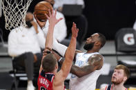 Los Angeles Lakers forward LeBron James, center, shoots as Washington Wizards center Moritz Wagner, left defends along with forward Davis Bertans during the first half of an NBA basketball game Monday, Feb. 22, 2021, in Los Angeles. (AP Photo/Mark J. Terrill)