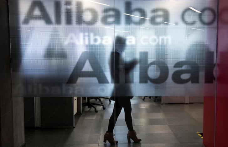 FILE PHOTO: An employee is seen behind a glass wall with the logo of Alibaba at the company's headquarters on the outskirts of Hangzhou, Zhejiang province