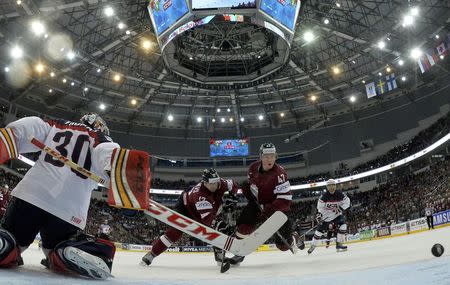 Goalie Tim Thomas of the U.S. is challenged by Latvia's Herberts Vasiljevs and Martins Cipulis (L-R) during their men's ice hockey World Championship Group B game at Minsk Arena in Minsk May 15, 2014. REUTERS/Alex Kudenko/Pool