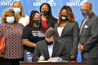 Kentucky Gov. Andy Beshear signs a bill creating a partial ban on no-knock warrants, Friday, April 9, 2021, at the Center for African American Heritage Louisville, Ky. At the signing is Tamika Palmer, the mother of Breonna Taylor, behind Governor left. The bill signing comes after months of demonstrations set off by the fatal shooting of Taylor in her home during a botched police raid. (AP Photo/Timothy D. Easley)