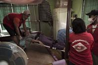 Noble Heart rescue ambulance charity service volunteers shift a patient to his home bedroom after taking him from a hospital in Yangon (AFP Photo/Nicolas Asfouri)