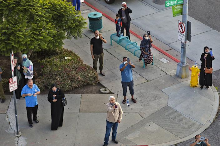 """People stop in their tracks to watch Mahmood Nadvi deliver the Islamic call to prayer from the roof of King Fahad Mosque in Culver City. <span class=""""copyright"""">(Irfan Khan / Los Angeles Times)</span>"""