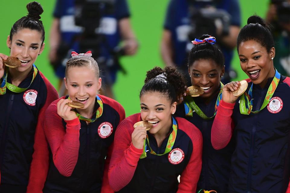 US gymnasts Alexandra Raisman, Madison Kocian, Lauren Hernandez, Simone Biles and Gabrielle Douglas celebrate with their gold medals on the podium during the women's team final Artistic Gymnastics at the Olympic Arena during the Rio 2016 Olympic Games in Rio de Janeiro on August 9, 2016. / AFP / Emmanuel DUNAND        (Photo credit should read EMMANUEL DUNAND/AFP via Getty Images)