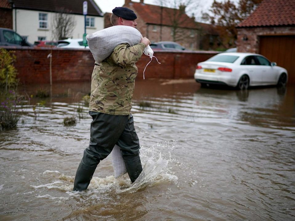 Soldiers help with sandbagging homes in the village of Fishlake (Getty)