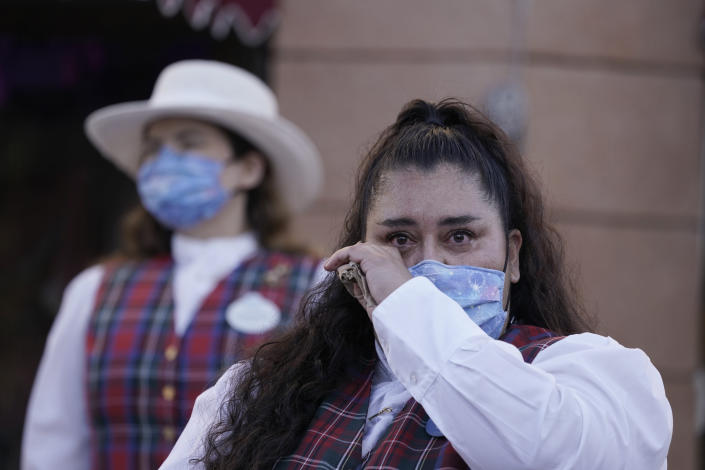 Employee Norali (last names not given), sheds a tear as they prepare to open the gates at Disneyland in Anaheim, Calif., Friday, April 30, 2021. The iconic theme park in Southern California that was closed under the state's strict virus rules swung open its gates Friday and some visitors came in cheering and screaming with happiness. (AP Photo/Jae Hong)