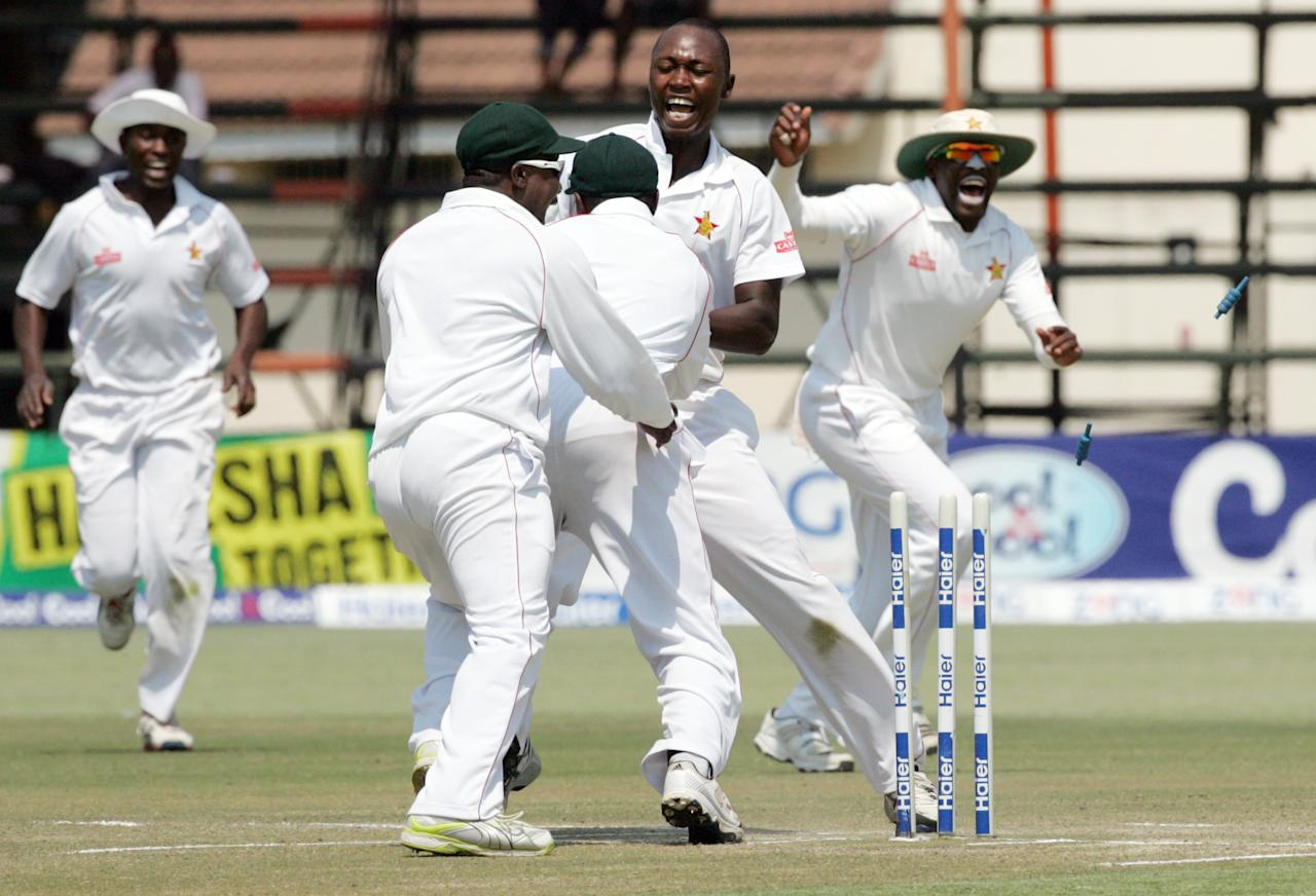 Zimbabwe players celebrate victory after effecting a stumping on September 14, 2013 during the fifth day of the second Test against Pakistan at the Harare Sports Club.                              AFP PHOTO / JEKESAI NJIKIZANA        (Photo credit should read JEKESAI NJIKIZANA/AFP/Getty Images)