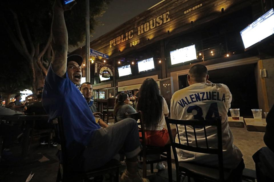 Dodgers fan Jose Manuel Zepeda cheers on a passing car honking in support of the Dodgers while watching the game