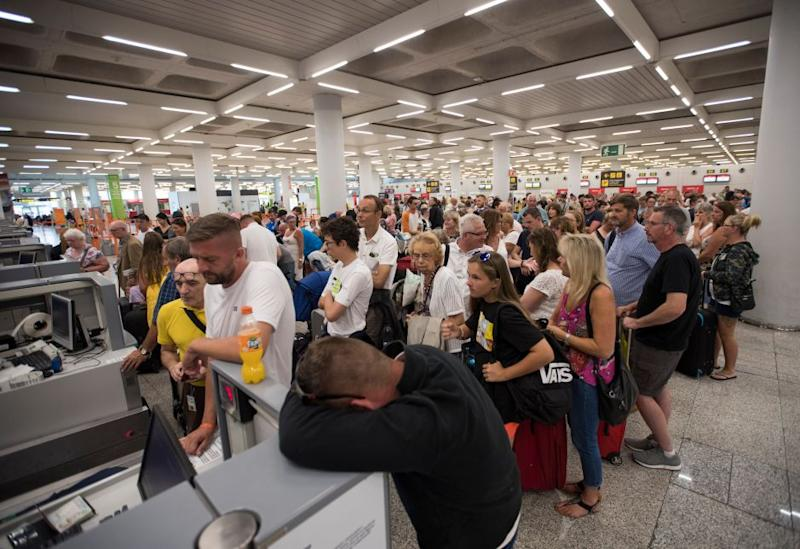 Passengers of British travel group Thomas Cook queue at Son Sant Joan airport in Palma de Mallorca on Sept. 23, 2019.