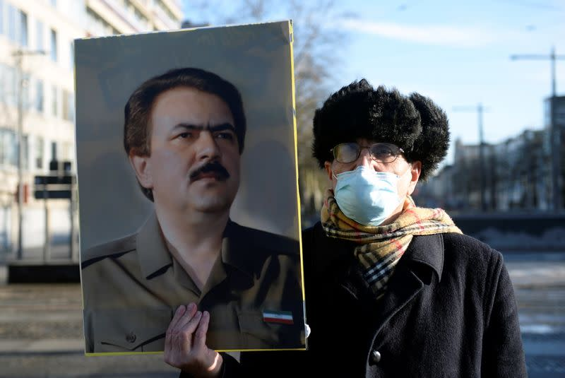 A man wearing a face mask holds a portrait of Iranian resistance leader Massoud Rajavi outside the court building in Antwerp
