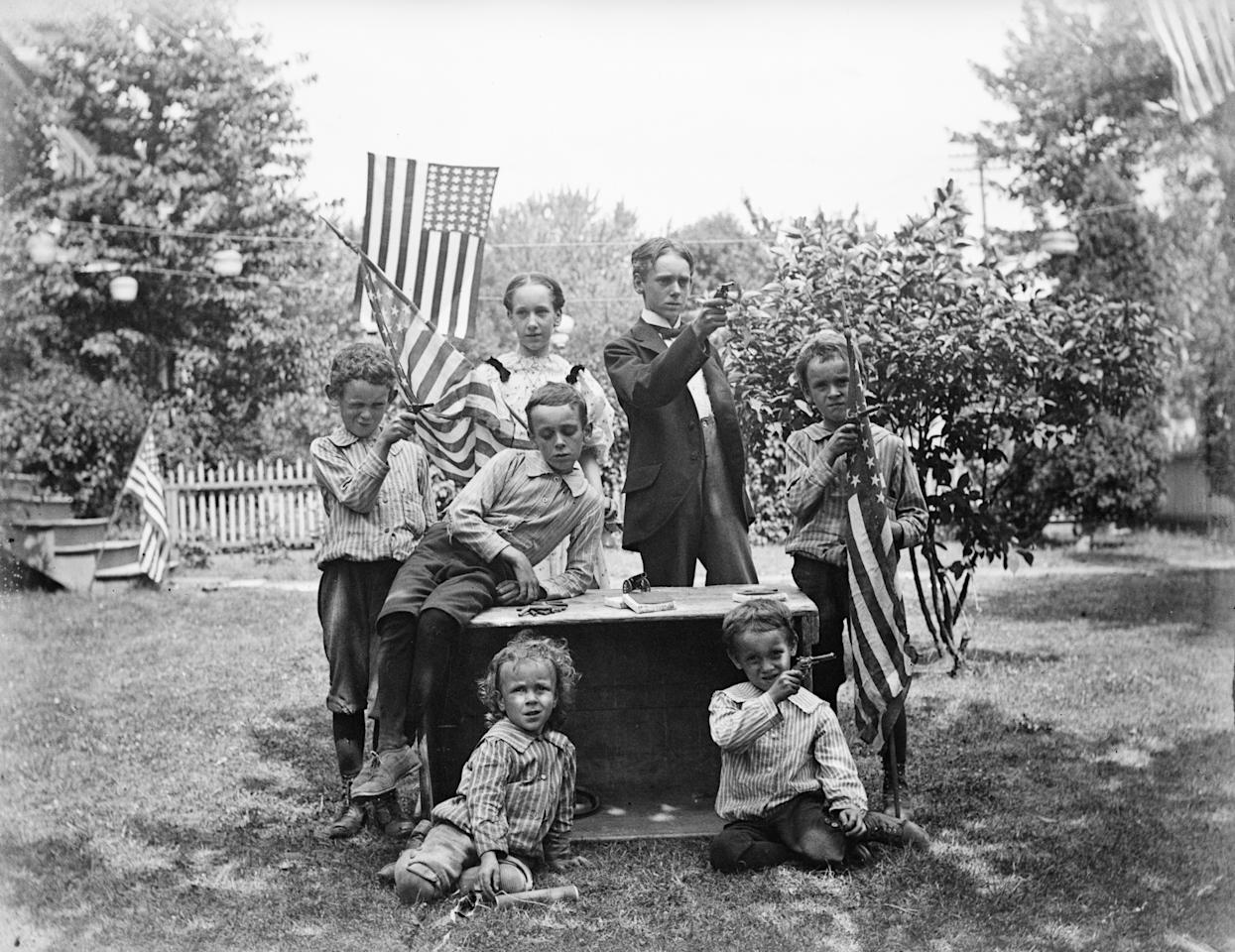 Family with pistols and flags get ready for their Fourth of July celebration circa 1880s