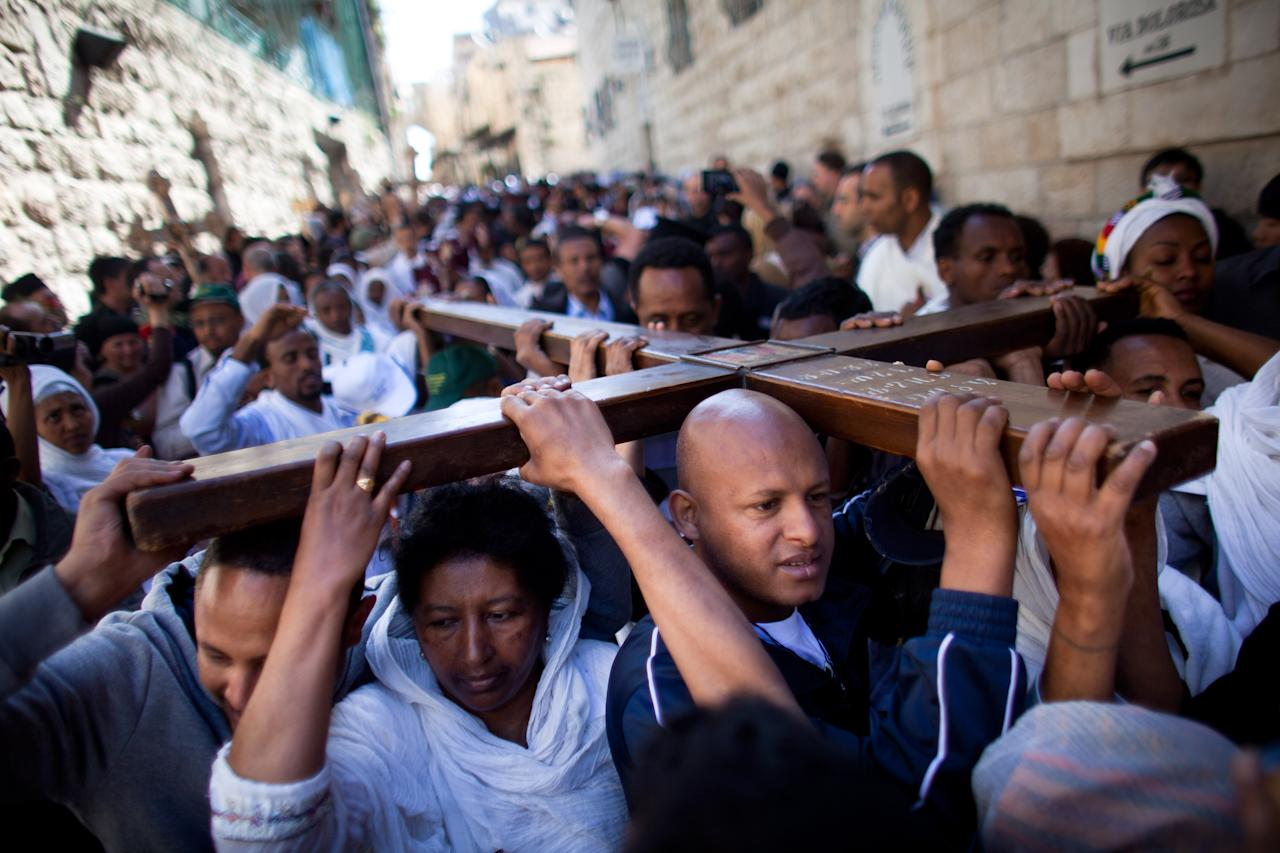 Orthodox Christian pilgrims hold wooden crosses as they take part in the Good Friday procession along the Via Dolorosa ahead of Orthodox Easter, on April 13, 2012 in Jerusalem's old city, Israel. Orthodox christians are celebrating Easter a week after Roman Catholics as dictated by the Julian calendar. Pilgrims are taking part in processions along the route that Jesus is believed to have taken in his last days as he carried the cross. (Photo by Uriel Sinai/Getty Images)