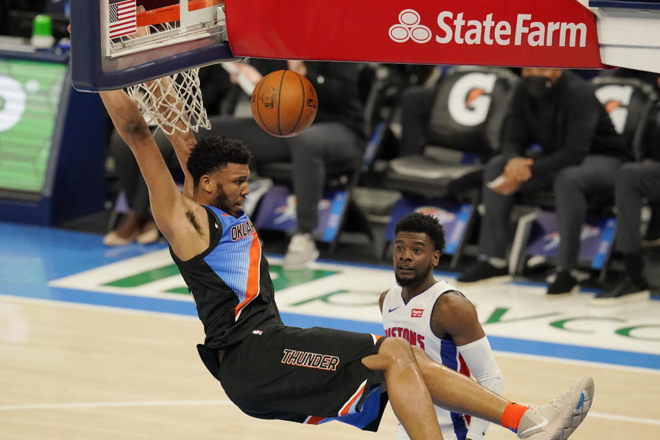 Oklahoma City Thunder center Tony Bradley, left, hangs from the basket after a dunk in front of Detroit Pistons guard Josh Jackson, right, in the first half of an NBA basketball game Monday, April 5, 2021, in Oklahoma City. (AP Photo/Sue Ogrocki)