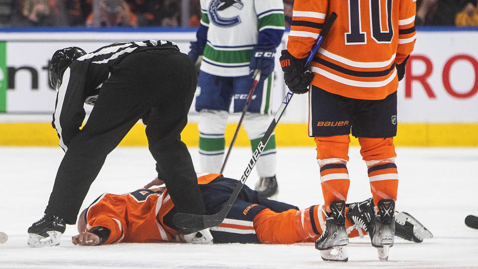 Edmonton Oilers' Zack Kassian (44) lies on the ice after a fight with Vancouver Canucks' Zack MacEwen (71). (THE CANADIAN PRESS/Jason Franson)