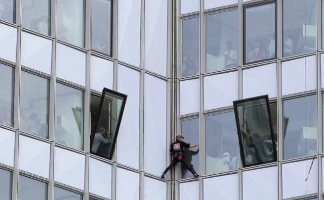 People look out of their windows as French urban climber Alain Robert, known as 'Spiderman', climbs up the 231 meter high (758 feet) First Tower, the tallest skyscraper in France, in the La Defense business district in Courbevoie, outside Paris, Thursday, May 10, 2012. (AP Photo/Michel Euler)