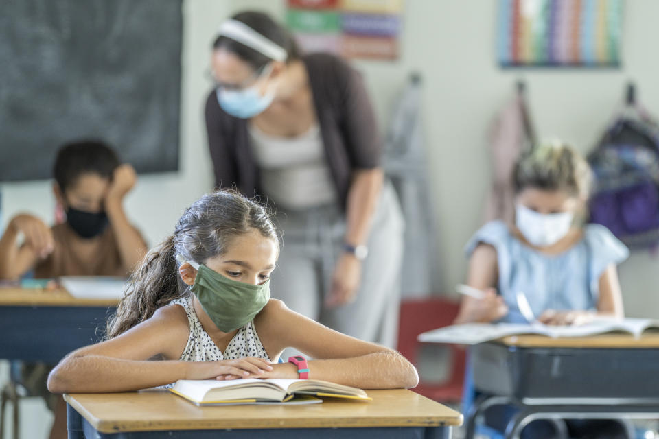 12 year old girl wearing a reusable, protective face mask in classroom while working on school work at her desk.