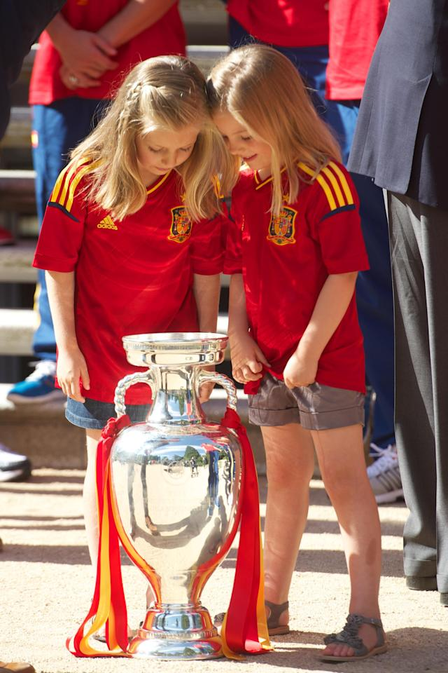 MADRID, SPAIN - JULY 02: Princess Leonor of Spain (L) and Princess Sofia of Spain peer into the UEFA EURO 2012 trophy as King Juan Carlos I of Spain receives players of Spain's victorious national football team at Zarzuela Palace on July 2, 2012 in Madrid, Spain. (Photo by Pool/Getty Images)