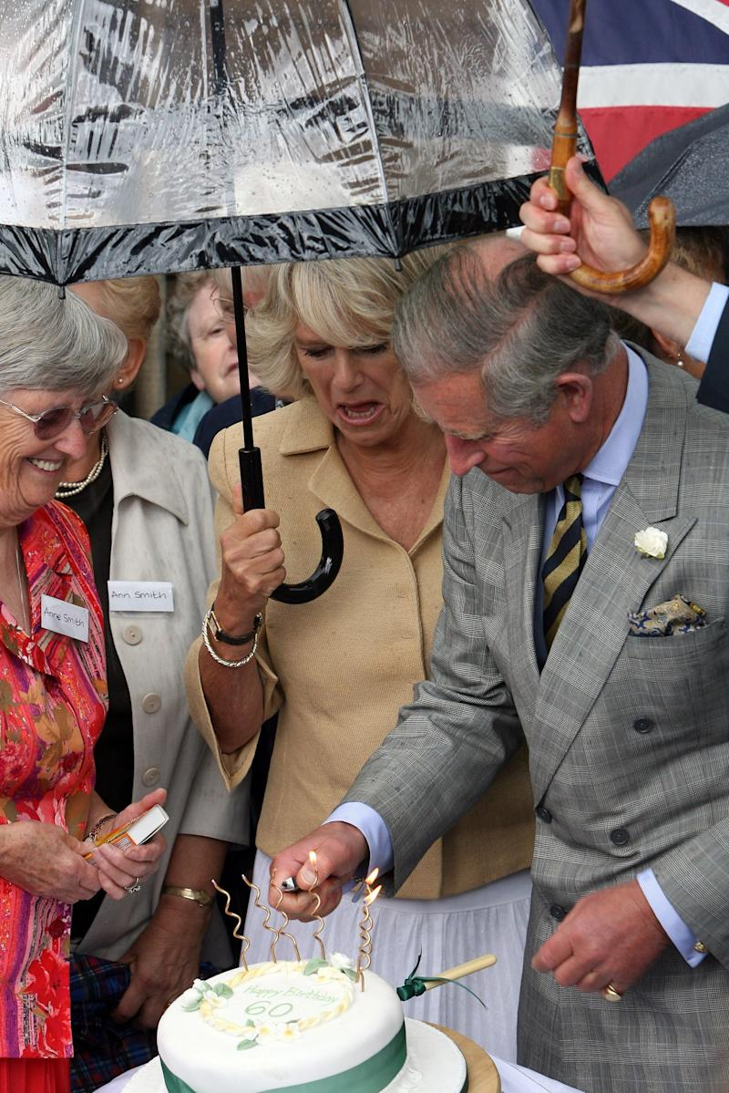 Camilla Parker Bowles reacting to Prince Charles lighting the candles of her 60th birthday cake during a visit to Bronham in Wiltshire, England, July 2007.