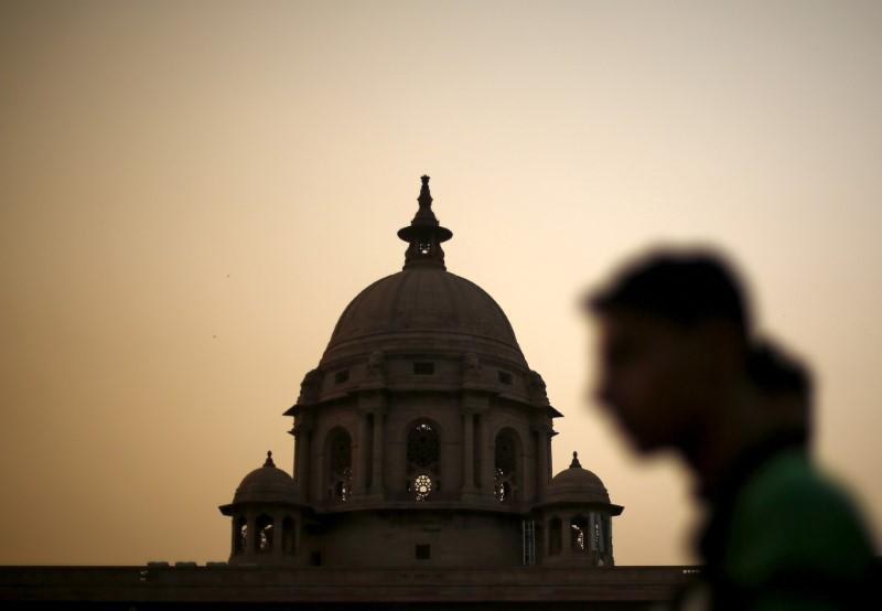 FILE PHOTO: A commuter walks past the building of India's Ministry of Finance during dusk in New Delhi