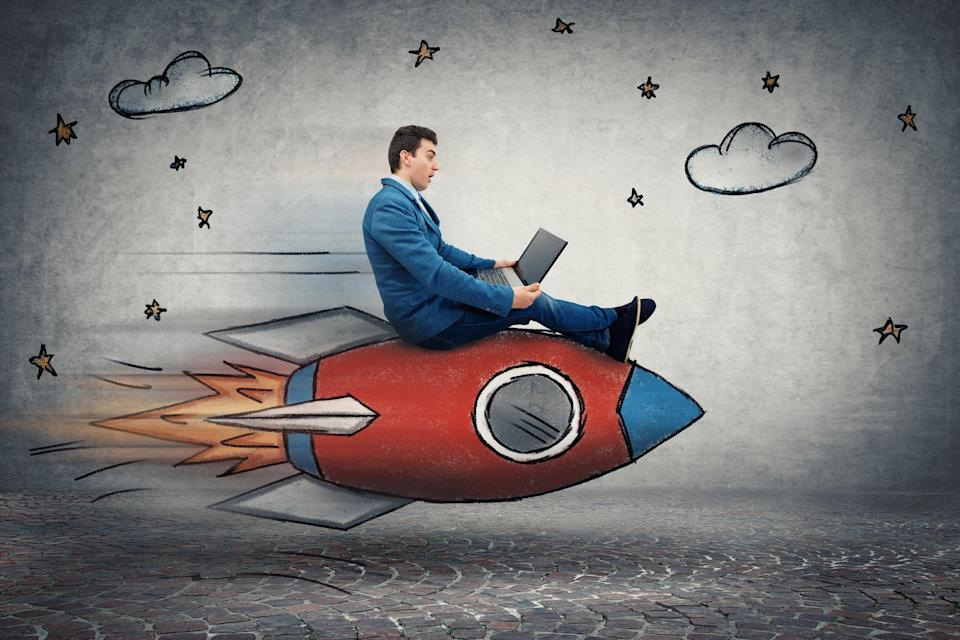 A man in a suit riding a toy rocket.