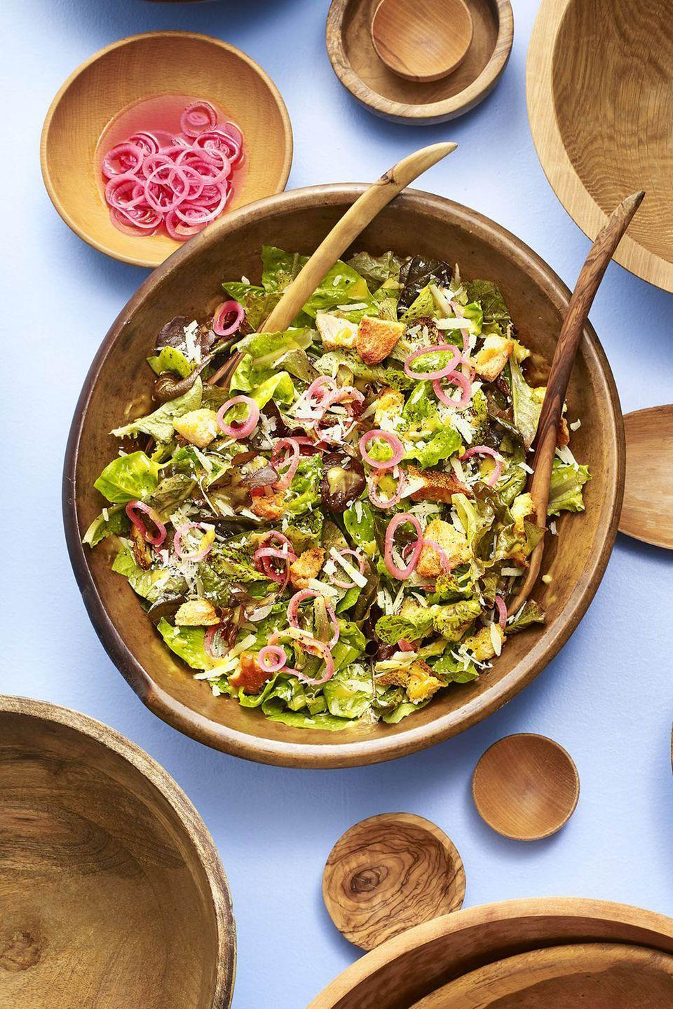 """<p>Upgrade Caesar salad with pickled shallots and homemade croutons.</p><p><strong><a href=""""https://www.countryliving.com/food-drinks/a19705324/spring-greens-caesar-salad-with-pickled-shallot-recipe/"""" rel=""""nofollow noopener"""" target=""""_blank"""" data-ylk=""""slk:Get the recipe"""" class=""""link rapid-noclick-resp"""">Get the recipe</a>.</strong></p><p><a class=""""link rapid-noclick-resp"""" href=""""https://www.amazon.com/Aidea-Acacia-Wooden-Salad-Bowl/dp/B076HN9Z8Z?tag=syn-yahoo-20&ascsubtag=%5Bartid%7C10050.g.3290%5Bsrc%7Cyahoo-us"""" rel=""""nofollow noopener"""" target=""""_blank"""" data-ylk=""""slk:SHOP SALAD BOWLS"""">SHOP SALAD BOWLS</a> </p>"""