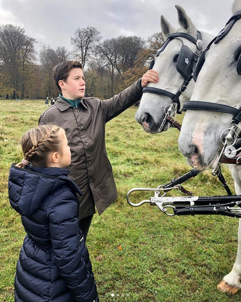 A photo of Prince Christian and Princess Josephine patting a horse at the annual Hubertus Hunt.