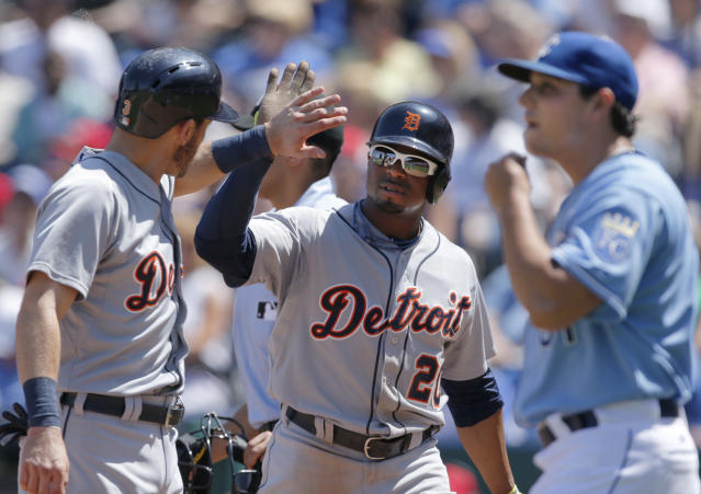 Detroit Tigers' Ian Kinsler, left, and Rajai Davis (20) celebrate after scoring on a doublehit by teammate Miguel Cabrera during the fourth inning of a baseball game against the Kansas City Royals in Kansas City, Mo., Sunday, May 4, 2014. Royals starting pitcher Jason Vargas, right, walks to the mound after the play. (AP Photo/Orlin Wagner)
