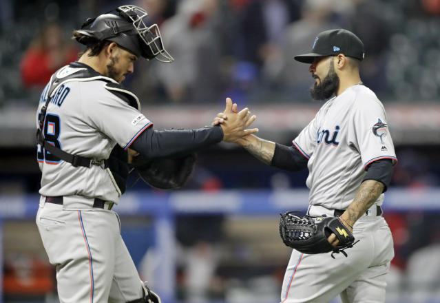 Miami Marlins relief pitcher Sergio Romo, right, is congratulated by catcher Jorge Alfaro after the Marlins defeated the Cleveland Indians 3-1 in a baseball game, Tuesday, April 23, 2019, in Cleveland. (AP Photo/Tony Dejak)