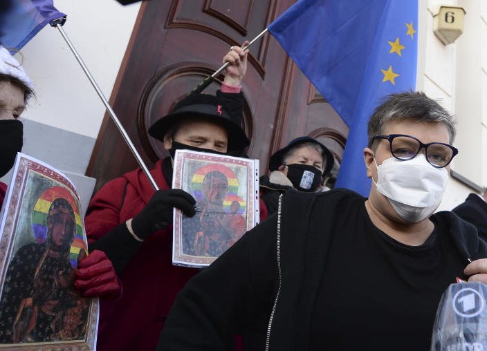 Polish activists Elzbieta Podlesna, right, is surround by supporters as she leaves the court after being acquitted of desecration by a court in Plock, Poland, Tuesday March 2, 2021. A Polish court has acquitted three activists who had been accused of desecration for adding the LGBT rainbow to images of a revered Roman Catholic icon. In posters that they put up in protest in their city of Plock, the activists used the rainbow in place of halos on a revered image of the Virgin Mary and baby Jesus. (AP Photo/Czarek Sokolowski)