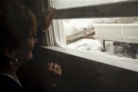 A woman looks out her window at the pounding surf during a winter nor'easter snow storm in Scituate, Massachusetts January 3, 2014. REUTERS/Dominick Reuter